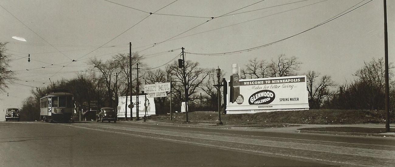 An advertisement for the Glenwood Inglewood Company on the border of St. Paul and Minneapolis from the late 1940's/early 1950's with a TCL streetcar passing by.