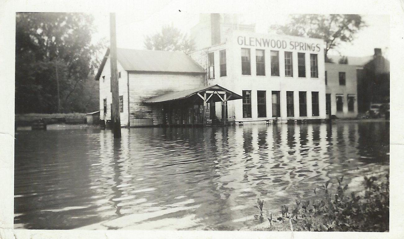 """A flood enveloped what is now part of the @glenwood parking lot in the 1940's. The space below the """"Glenwood Springs"""" sign is home to Top Source Media today, to the right is the headquarters for Tamble Inc. and in the background the Fruen Mill is faintly visible."""